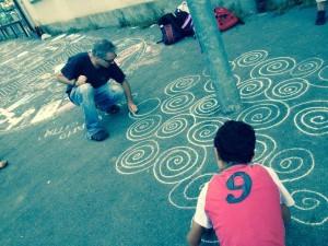 I ragazzi di ArchiBAR decorano con i gessetti un marciapiede di Barriera di Milano assieme ad Alessandro Bulgini.