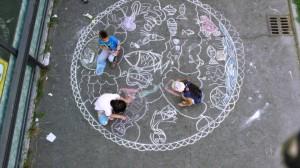 Alessandro Bulgini, assieme ai ragazzi di ArchiBAR, decora con i gessetti un marciapiede di Barriera di Milano .